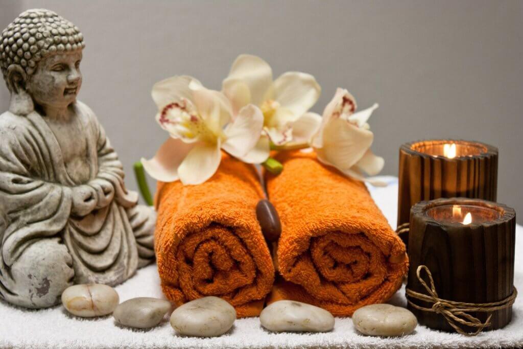 Tonis Hotel Wellness. Zwei Badesets (Handtuch und Kerze), links eine Buddah-Figurine. Dazu Lotosblüten.